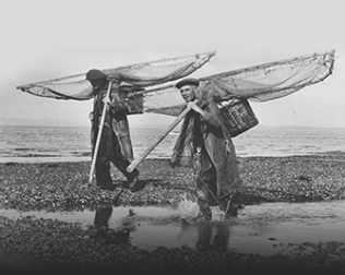 Fishing with push nets for shrimps.. Two men wearing caps carry nets over their left shoulders. |  LM88.110.3097 Courtesy of Lancaster Maritime Museum, part of Lancashire County Council Museum Service.