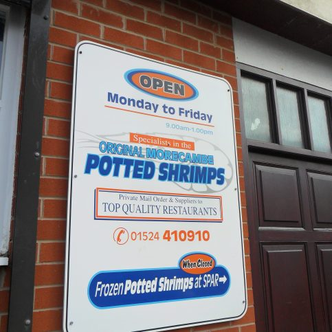 Photo of shop front sign at Baxter's fish shop giving details of opening hours and indicating that they are specialists in supplying Morecambe Bay potted shrimps.