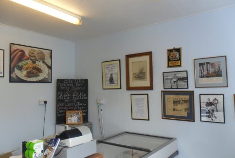 Photo of Baxter's fish shop interior showing the cash till, the serving counter, a chalk board listing items for sale and various photos on the wall.