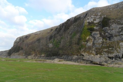 View of cliff at Humphrey Head and grassy area on beach.