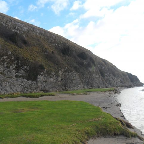 View of cliff and channel at Humphrey Head and grassy area on beach.