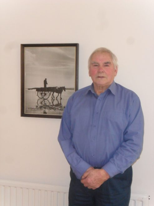 Photograph of Jack Manning, interviewee for oral history project, with photograph on wall behind him of a fisherman stood on the back of a horse and cart on the sands.