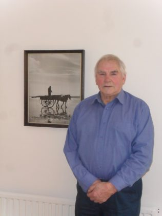 Photograph of Jack Manning, interviewee for oral history project, with photograph on wall behind him of a fisherman stood on the back of a horse and cart on the sands (version 2).