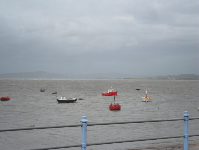 View of sea with the tide in and seven small boats from the promenade at Morecambe.