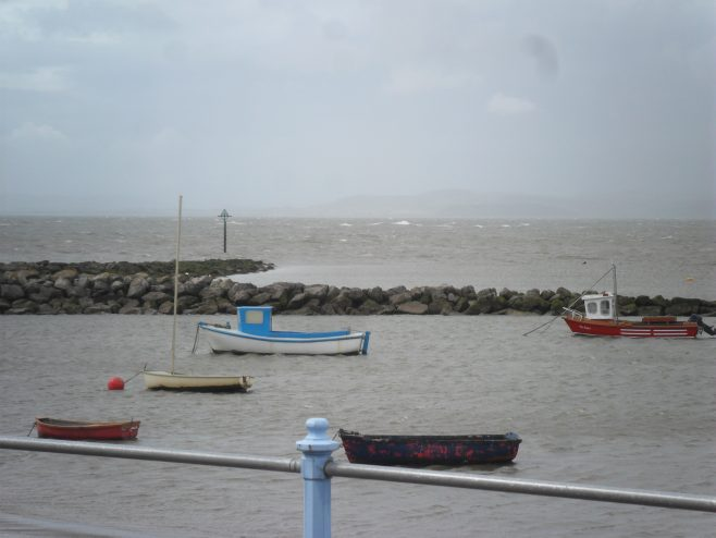 View of the breakwater and sea with the tide in and five small boats from the promenade at Morecambe.