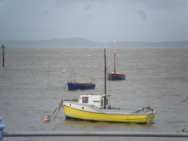 View of the sea with the tide in and a small fishing boat in the foreground from the promenade at Morecambe.