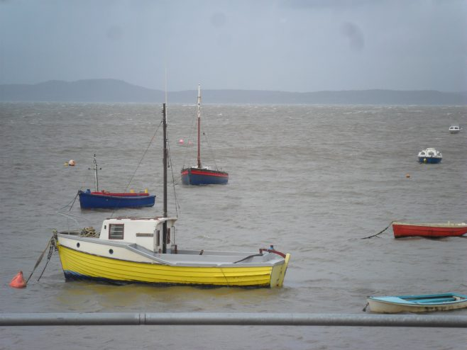 View of the sea with the tide in, three small fishing boats and four other boats from the promenade at Morecambe.