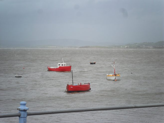 View of the sea with the tide in and five small boats from the promenade at Morecambe.