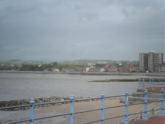 View of the sea and Bare sea front from the promenade at Morecambe, showing Princes Crescent flats far right.