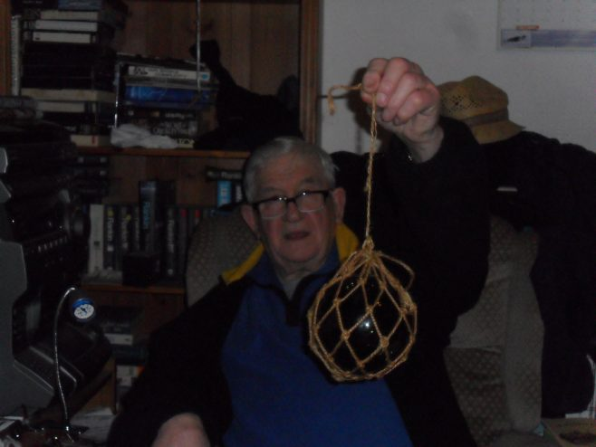 Ernie Nicholson holding up a glass fishing float in netting.