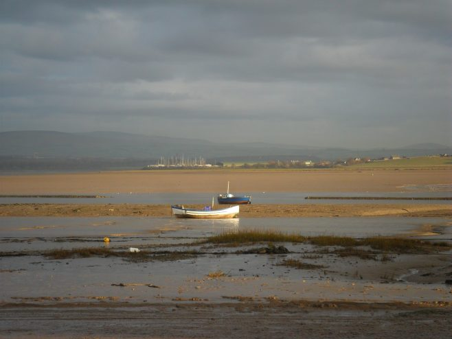 View across the River Lune from Sunderland Point across to Glasson Dock, with the yachts in the marina just visible in the distance and two small boats in the foreground.