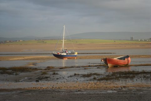 View across the River Lune from Sunderland Point across to Glasson Dock, with a pleasure yacht and a local fishing boat in the foreground and the Bowland Fells in the background.