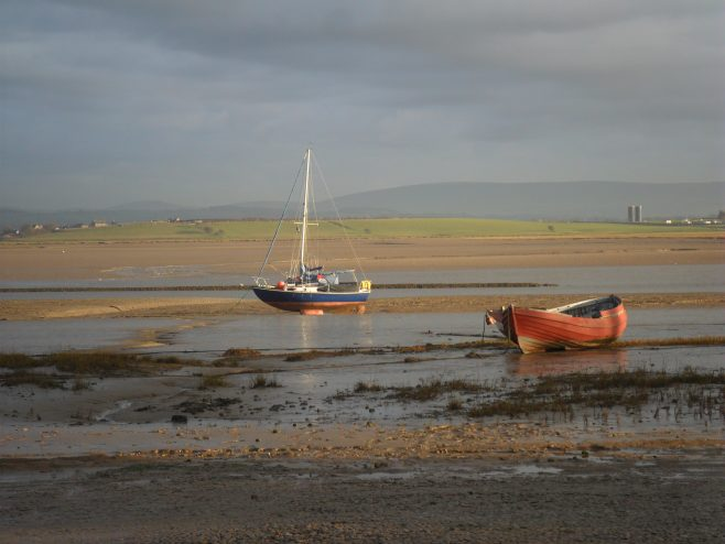 View across the River Lune from Sunderland Point across to Glasson Dock, with a small fishing boat and a rowing boat in the foreground and the Bowland Fells in the background.