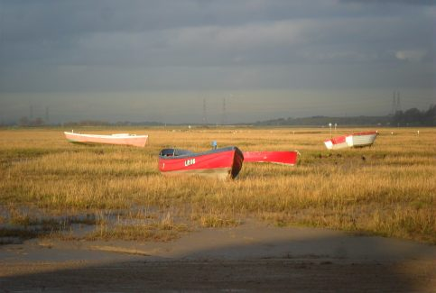 View from Sunderland Point showing four local fishing boats at low tide on grassy bank and electricity pylons in distance.