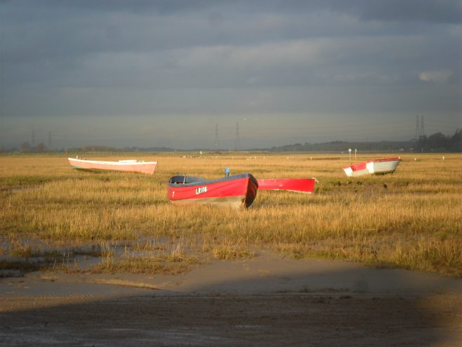 View from Sunderland Point showing 4 small boats at low tide on grassy bank and electricity pylons in distance.