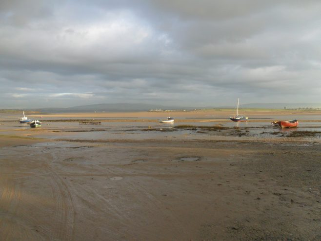 The Lune estuary at Sunderland Point showing five small boats.