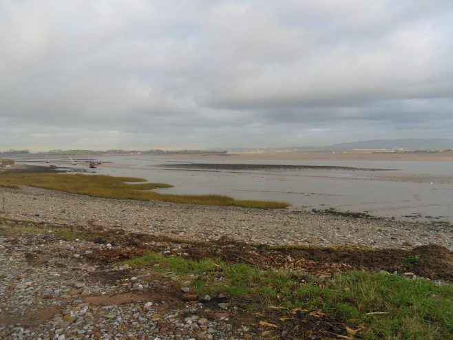 View of Lune estuary at Sunderland Point at low tide with rocky shore in foreground.