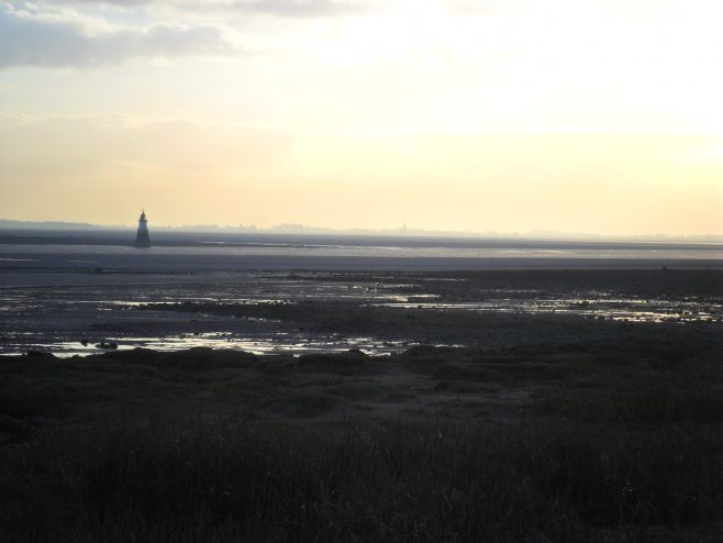 Plover Scar lighthouse seen from Sunderland Point at dusk.
