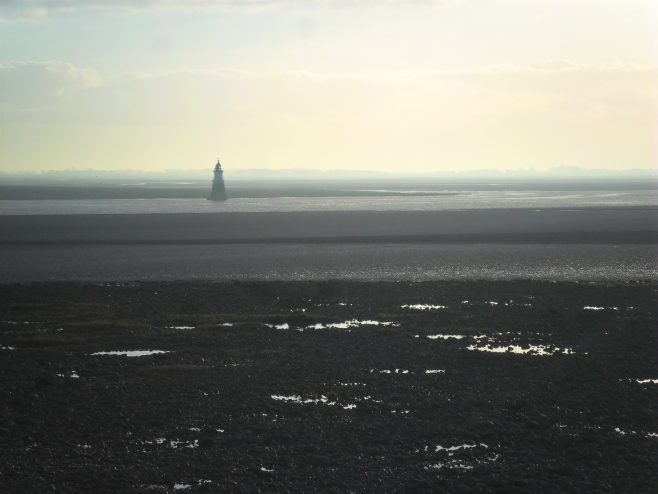 View of Plover Scar lighthouse from Sunderland Point at dusk.