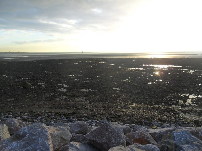 View of the rocky shore taken at sunset at Sunderland Point with Plover Scar lighthouse in the far distance.