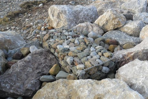 Close up image of a gabion, a wire cage filled with stones for defence against coastal erosion.