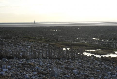 View of wooden sea groynes and rocky shore at Sunderland Point with Plover Scar lighthouse in the distance.