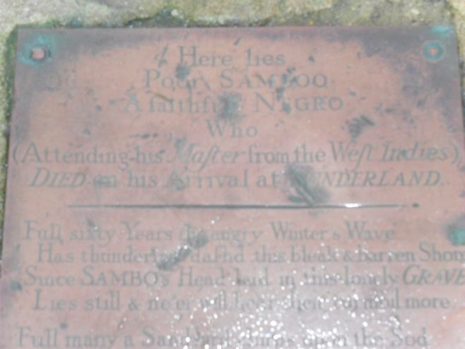 Close-up of top half of plaque on Sambo's Grave at Sunderland Point showing some of the lettering on the grave marker.