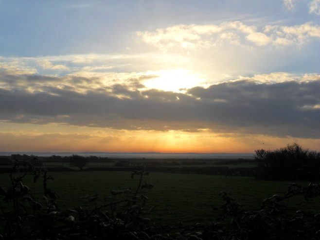 Sunset at Sunderland Point with fields in the foreground.