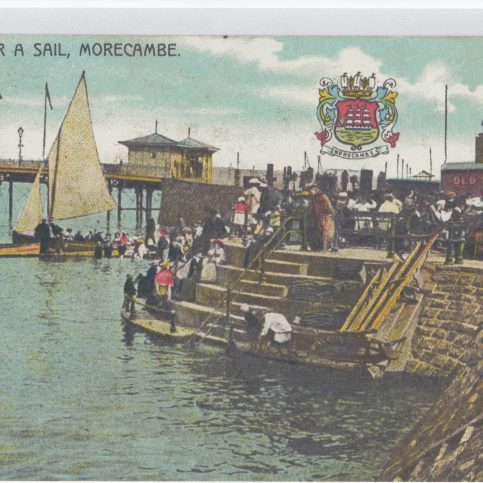 Laden Morecambe Bay pleasure boat in the background, with people waiting to board on the steps