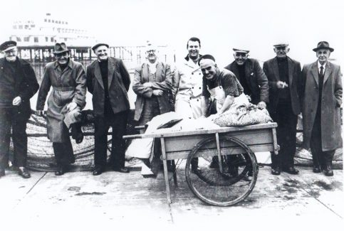 Morecambe fishermen pose for a photograph with Central Pier in the background
