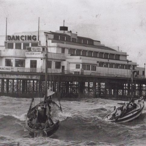 Fisherman's lifeboat the Sir William Priestley tows a Morecambe boat in rough sea along side Central Pier
